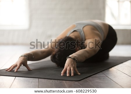 Young beautiful sporty yogi woman practicing yoga concept, sitting in Child exercise on black yogic mat, Balasana pose, working out, wearing sportswear, white studio or home background, wooden floor #608229530