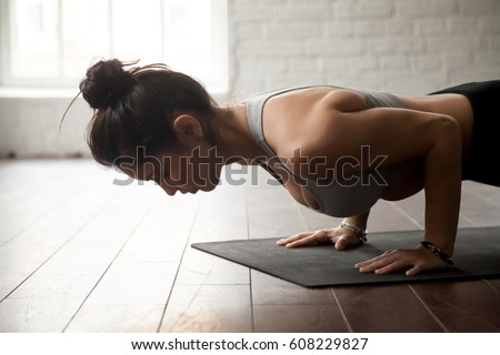 Young attractive woman practicing yoga, standing in chaturanga dandasana exercise, four limbed staff, Push ups or press ups pose, working out, white loft studio background, closeup #608229827