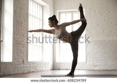 Young attractive woman practicing yoga, standing in Natarajasana exercise, Lord of the Dance pose, working out, wearing sportswear bra and pants, white loft studio background, full length, side view #608234789