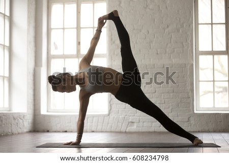 Young yogi woman practicing yoga concept, standing in Full Version of Vasisthasana exercise, Side Plank pose, working out, wearing sportswear, full length, white loft studio background, side view #608234798