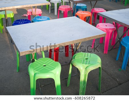Outdoor metal table and colored plastic chair, street food scene in Thailand #608265872