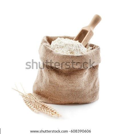 Bag with flour and wooden scoop on white background Royalty-Free Stock Photo #608390606