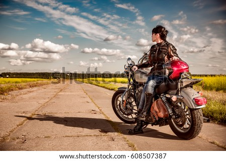 Biker girl in a leather jacket on a motorcycle #608507387