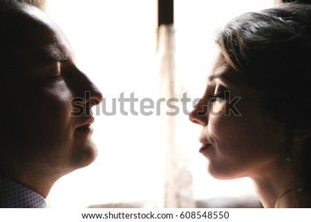 Profile of man and woman with closed eyes sitting before the bright window #608548550
