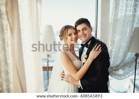 Handsome brunette groom and dark blonde bride hug before bright window #608565893