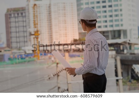 Attractive of Asian Man at construction engineer site with hard hat holding blue print paper  #608579609