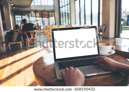 Mockup image of a woman using laptop with blank white screen on wooden table in modern loft cafe #608590433