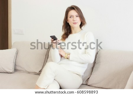 Beautiful young woman watching television sitting surrounded by cushions on a comfortable sofa with the remote control in her hand #608598893