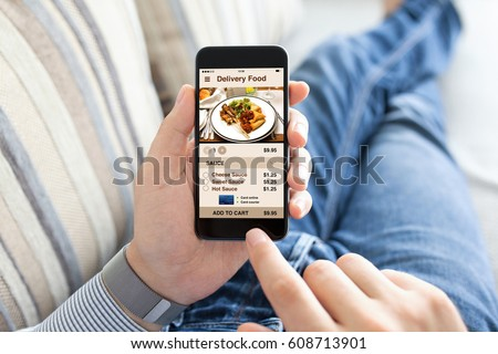 man lying on sofa and holding phone with app delivery food screen Royalty-Free Stock Photo #608713901