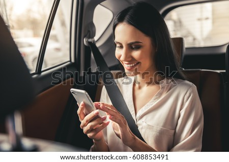 Beautiful business woman is using a smart phone and smiling while sitting on back seat in the car #608853491