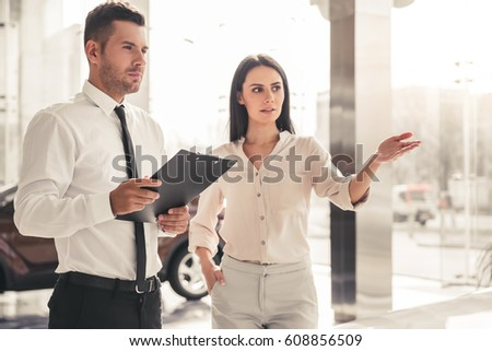 Beautiful young woman is talking to handsome car dealership worker while choosing a car in dealership #608856509