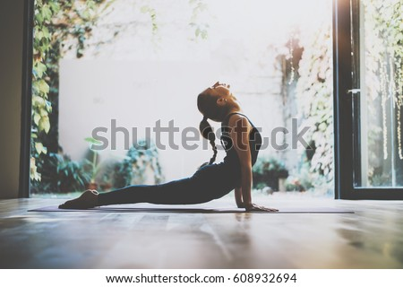 Portrait of gorgeous young woman practicing yoga indoor. Beautiful girl practice cobra asana in class.Calmness and relax, female happiness.Horizontal, blurred background.Visual effects #608932694