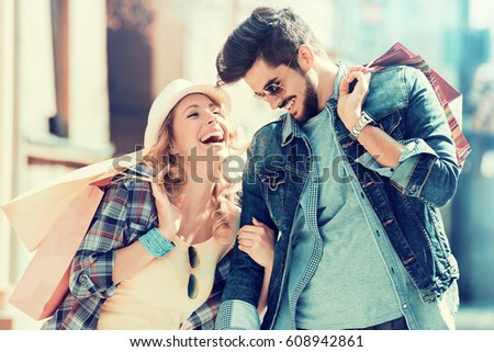 Young happy couple with shopping bags in the city. Royalty-Free Stock Photo #608942861