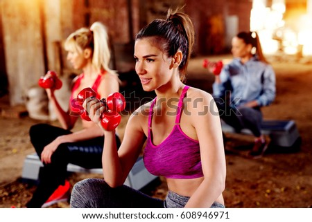 Working biceps with dumbbells attractive females exercising in group. Strong woman. #608946971