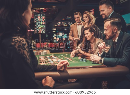 Upper class friends gambling in a casino Royalty-Free Stock Photo #608952965