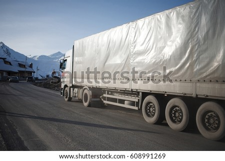 White refrigerated truck on winter road on background of the mountains. #608991269