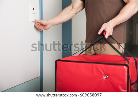 Pizza Delivery Man Ringing The Door Bell With A Large Red Bag In His Hand #609058097