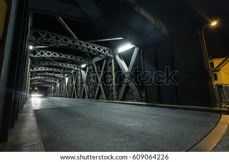 Asphalt road under the steel construction of a bridge in the city. Night urban scene with car light trails in the tunnel. Toned #609064226
