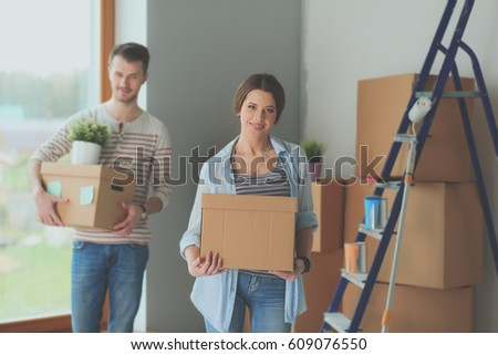 Happy young couple unpacking or packing boxes and moving into a new home #609076550