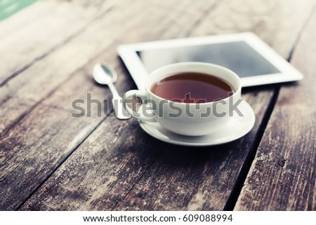 Digital tablet and cup of coffee on old wooden desk. Simple workspace or coffee break in morning/ selective focus #609088994