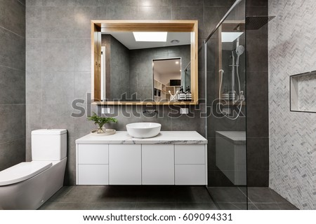 Modern grey designer bathroom with herringbone shower tiling Royalty-Free Stock Photo #609094331