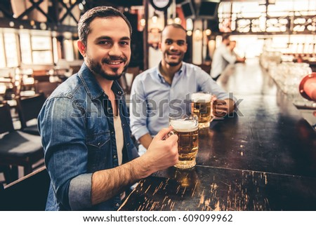 Handsome guys are drinking beer, looking at camera and smiling while resting in pub #609099962