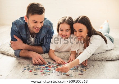 Charming little girl and her beautiful young parents are doing jigsaw puzzle and smiling while lying on the floor at home Royalty-Free Stock Photo #609100568