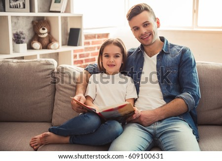 Charming little girl and her handsome young dad are reading a book and smiling while sitting on sofa at home #609100631
