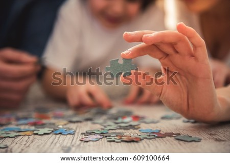 Little girl and her young parents are doing jigsaw puzzle while lying on the floor at home Royalty-Free Stock Photo #609100664