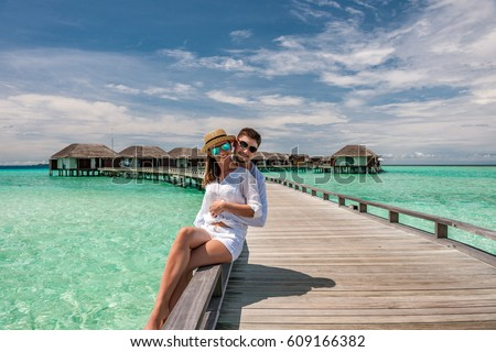Couple in white on a tropical beach jetty at Maldives #609166382