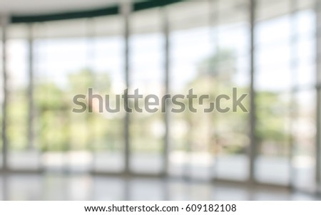 Business blur background interior view empty office lobby hallway glass wall with blurry light bokeh