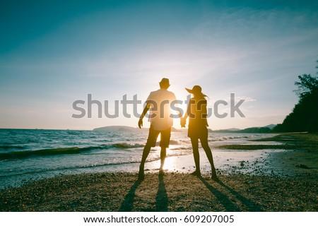 Romantic middle aged couple enjoying beautiful sunset walk on the beach travel vacation, Krabi Thailand #609207005