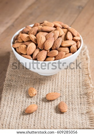 Almond snack fruit in white bowl on wooden table background #609285056