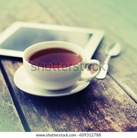 Digital tablet and cup of coffee on old wooden desk. Simple workspace or coffee break in morning/ selective focus #609312788