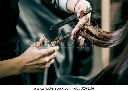 Scissors cut the girls hair, brunette Royalty-Free Stock Photo #609324134