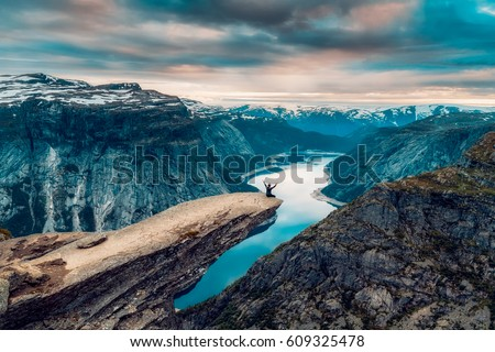 A man sits while throwing his arms in the air on the mountain's cliff edge of Trolltunga throning over Ringedalsvatnet watching the sunset in the snowy Norwegian mountains near Odda, Rogaland, Norway. #609325478