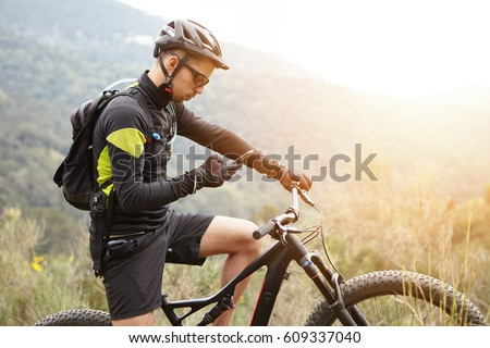 People, sports, active lifestyle and modern technology. Outdoor picture of cyclist on booster bike using navigator on smart phone, exploring map and searching GPS coordinates while biking in mountains