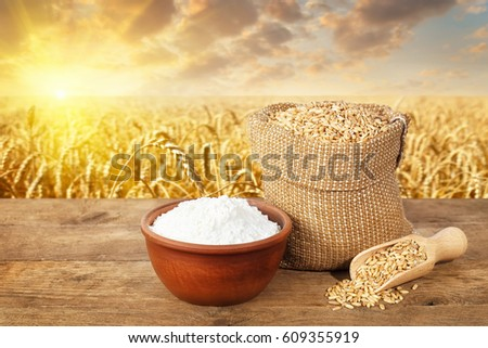 wheat grains in bag and flour in bowl on table with ripe cereal field on the background #609355919