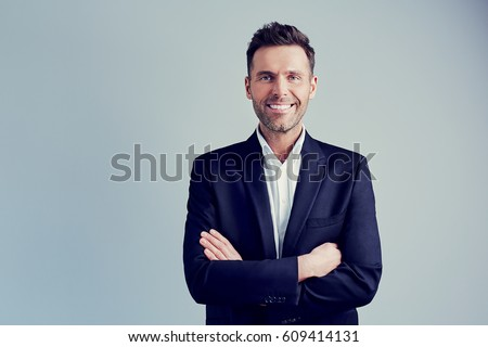 Happy businessman isolated - handsome man standing with crossed arms #609414131