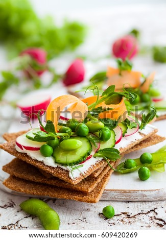 Healthy sandwiches with soft cheese and raw spring vegetables on crisp rye bread #609420269