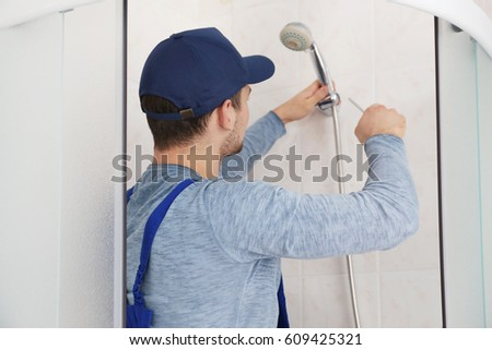 Plumber working in shower stall #609425321