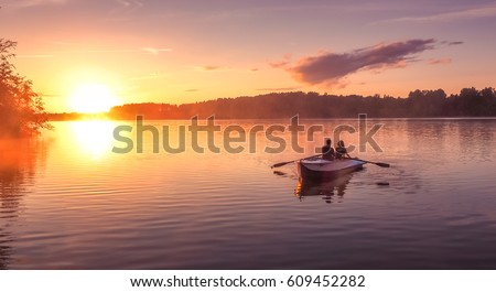 A beautiful golden sunset on the river. Lovers ride in a boat on a lake during a beautiful sunset. Happy couple woman and man together relaxing on the water. The beautiful nature around.  #609452282