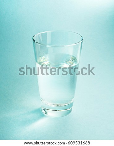 A glass of pure cool water on a textured light blue background close-up with beautiful light and highlights . #609531668