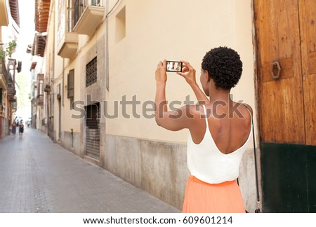 Rear view of african american tourist woman visiting a picturesque city street destination, using a smart phone taking pictures on summer holiday, outdoors. Black woman travel technology recreation.