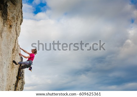 Female climber hanging by a cliff #609625361