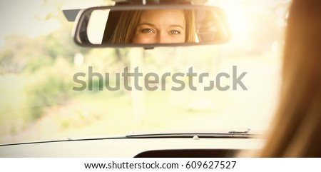 Young woman in the drivers seat looking in the mirror in her car #609627527
