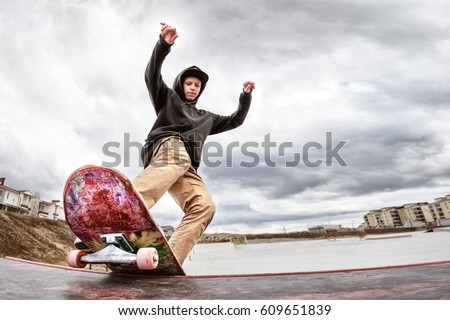 Teen skater in a hoodie sweatshirt and jeans slides over a railing on a skateboard in a skate park #609651839