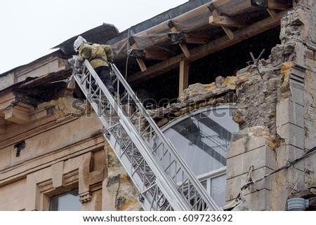 ODESSA, UKRAINE - MARCH 26, 2017: Rescuers on fire truck from fire staircase eliminate consequences of collapse of part of house as result of an earthquake.   #609723692