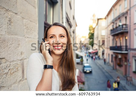 Young european woman calling phone standing on balcony and looking on street #609763934