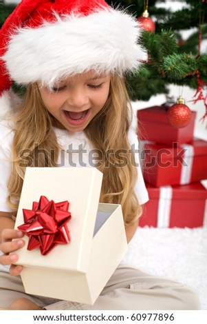 Excited little girl opening christmas present in front of the fir tree - closeup